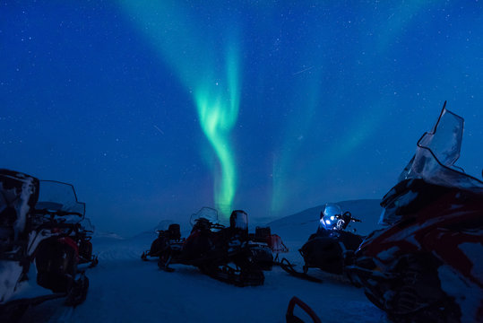 The polar arctic Northern lights aurora borealis sky star in Norway Svalbard in Longyearbyen the snowmobile mountains