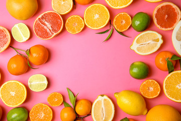 Frame made of different citrus fruits on color background, top view. Space for text