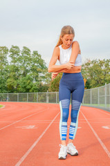 Fitness woman on running track has elbow pain during workout