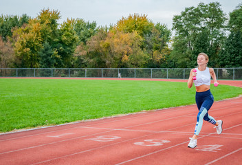 Healthy lifestyle. Woman runner with dumbbells is running outdoor