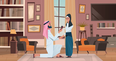 arab man kneeling holding engagement ring proposing arabic woman marry him couple in love wedding marriage offer happy valentines day concept living room interior