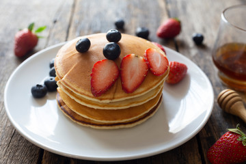 Delicious pancakes with Strawberry and blueberry on wooden table.top view