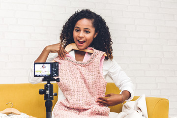 African american woman blogger in front of camera recording vlog herself talking about with clothes at home.fashion shopping and social media concept