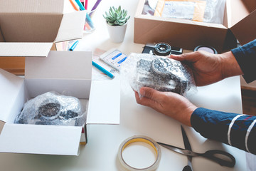 Online shopping concepts with young person wrapping product to the box.Ecommerce,shipping delivery service.Business retail