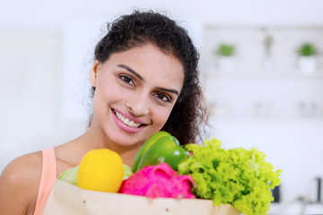 Attractive woman holding fresh vegetables