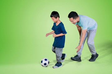 Child and father playing football in the studio