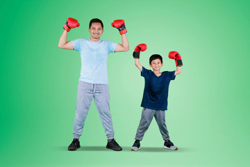 Child and father wearing boxing gloves on studio