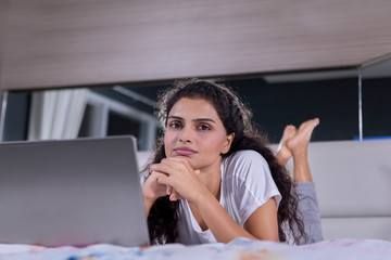 Curly hair woman lying with a laptop on the bed
