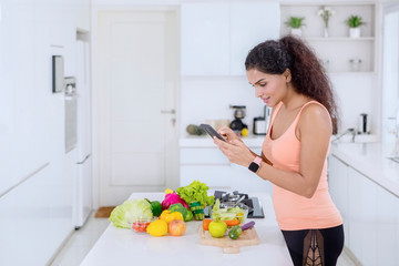 Curly hair woman using a phone in the kitchen