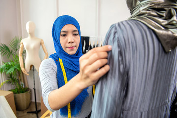 Asian muslim woman designer working in her tailor shop