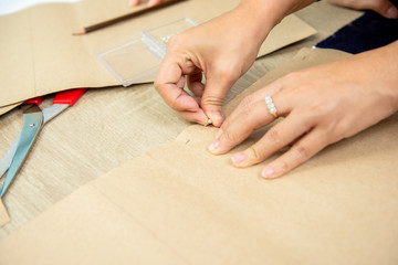 Hands of woman designer pinning paper pattern on fabric