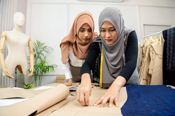 Muslim woman fashion designer pinning paper pattern on fabric