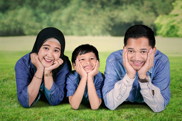 Happy Muslim family lying together in the park