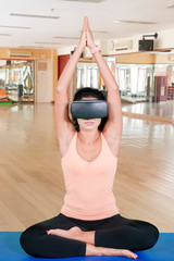 Indian woman meditates with virtual reality glasses