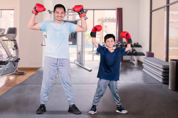 Little boy and his father wear boxing gloves