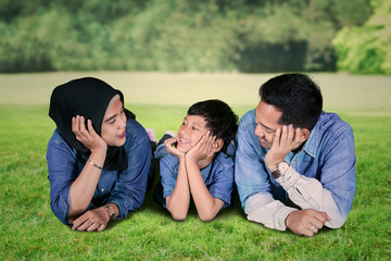 Little boy lying in the park with his parents