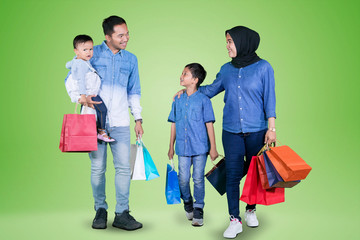 Muslim family holding shopping bags in the studio