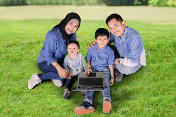 Parents and children using a laptop in the park