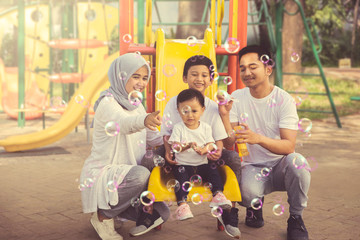 Parents play soap bubbles with their children