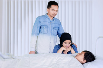 Sad parents visiting their sick son in the clinic