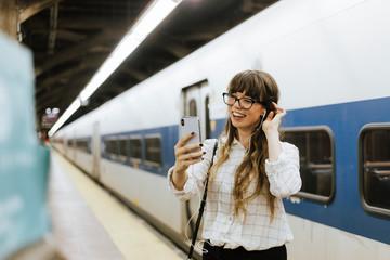 Cheerful woman having a video call at a subway platform