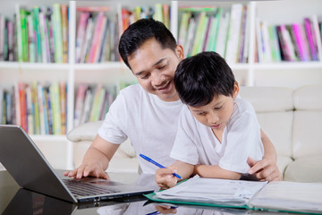 Young father helps his son to study in the library