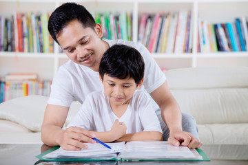 Young man guiding his son to study