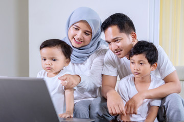 Young Muslim family using a laptop at home