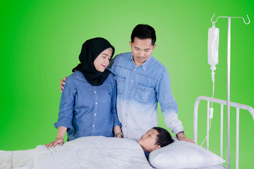 Young parents accompanying their sick son