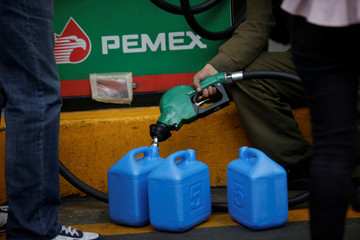 An employee fills a plastic tank with fuel at a petrol station in Mexico City
