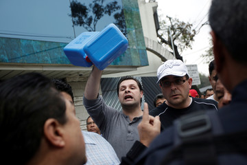 A man hold up plastic tanks outside at a gas station in Mexico City