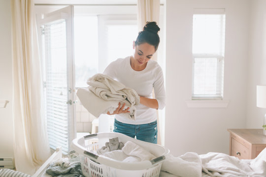 A woman folding laundry in a bright white bedroom.