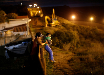 A migrant from Honduras, part of a caravan of thousands from Central America trying to reach the United States, helps a child to jumps the fence to cross it illegally from Mexico into the U.S., in Tijuana,