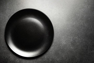 Gray stone table, black empty plate. View from above. Place for text