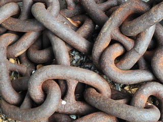 Oval rusty links of massive old unused chain laying on ground in pile.