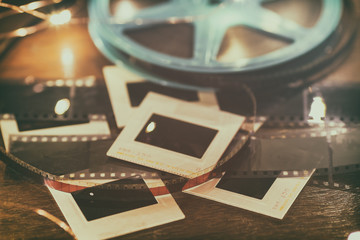 Photo slides, film negatives and 8mm or super 8 vintage film reel on a wood table with soft lights.