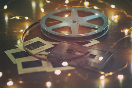 Photo slides, cassette audio tape and a 8mm or super 8 vintage film reel on a wood table with soft lights.