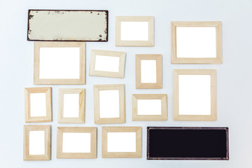 Multiple many blank small picture frames made of wood on white wall