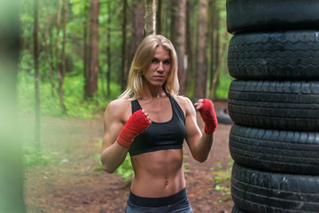 Woman boxer professional fighter posing in boxing stance, working out outdoors