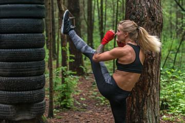 Woman fighter practising martial arts performing a leg axe kick working out outdoors