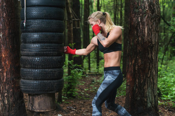 Woman boxer doing uppercut kick working out outdoors.