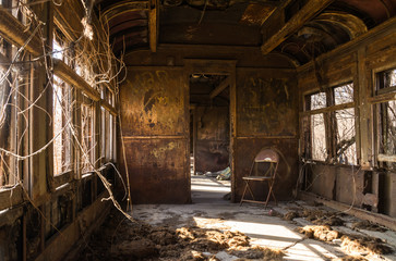 Interior of rusted vintage rail car with natural light coming through the windows.