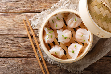 Homemade dumplings dim sum with stuffed shrimp close-up in a bamboo steamer box. horizontal top view