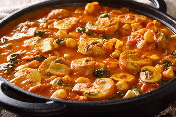 Hot Asian mushroom curry with spinach and chickpeas close-up in a pan. horizontal