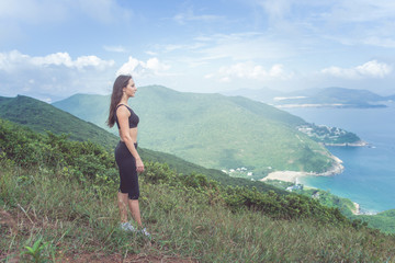 Sporty young woman standing on hill admiring the view of sea and green mountains in sunlight