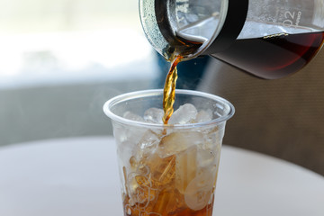 Pouring fresh brewed coffee from coffee pot into plastic glass of ice. Cold summer drink with copy space