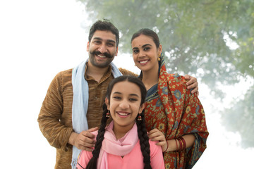 Portrait of a smiling village man standing with his wife and daughter posing for a family photo.