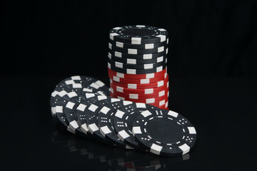 stack of casino chips in black and red, on a dark background, with reflection