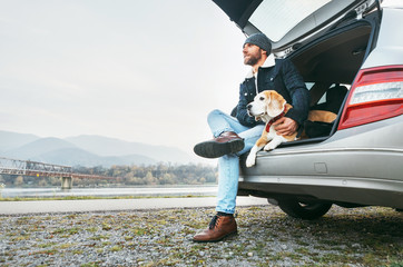 Breaded man in warm clothes siting with beagle in car trunk. Traveling with pet concept image