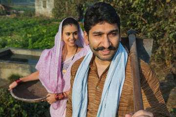 Close up of a village man going to agriculture field carrying a spade with his wife following him with an iron gold pan in hand.